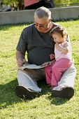 The grandfather with grand daughter sitting on a grass in park