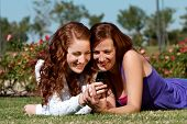 Two girlfriends in park with a mobile phone