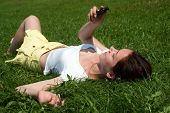The young girl with a mobile phone laying on a grass