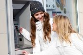 stock photo of automatic teller machine  - Happy girls withdrawing money from credit card at ATM - JPG