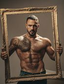 Latin Man With Muscular Body Holds A Frame And Looks Seriously. Muscular Latin Lover. Handsome Bruta poster