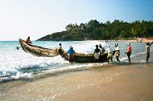 KOVALAM, INDIA - JANUARY 20 : Fishermen bring their traditional boat to the sea against waves January 20, 2009 in Kovalam, Kerala,  India.