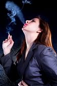 Close up business woman with cigarette .Photo-session in studio isolated on dark background
