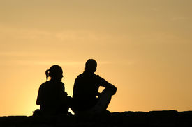 stock photo of male female  - Silhouetted loving couple at sunset - JPG