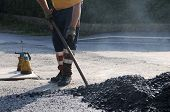 picture of road construction  - man with shovel is working on a road construction - JPG
