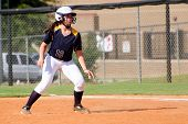 picture of fastpitch  - Young teen girl playing softball in organized game - JPG