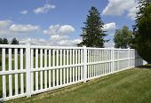 picture of puffy  - white vinyl fence by green lawn with a evergreen trees and a bright blue sky overhead with white puffy clouds - JPG
