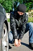 Homem da máscara de puncturas um pneu de carro. Conceito de vingança