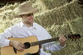 Guy Playing Country And Western Music On Guitar In Barn