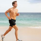 Fitness sports runner man jogging on beach. Handsome young fit sporty male athlete running outside o