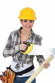 cute female carpenter using handsaw
