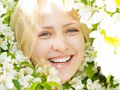 Closeup laughing woman among blossom tree