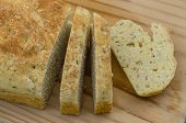 picture of baking soda  - Close Up view of a Loaf of Herb and Garlic Soda Bread Sliced and presented on a Bread Board - JPG