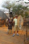 Zulu Chief posing with tourist in Shakaland Zulu Village, South Africa