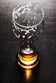 drained glass of fresh lager beer on black table