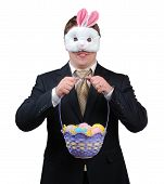 stock photo of peter cottontail  - Young man wearing suit with Easter Bunny mask holding an Easter basket full of brightly coloured eggs - JPG