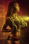 Young sports woman with heavy chain. Vibrant red colors.