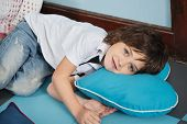 Portrait of little boy lying on heartshaped pillow in preschool