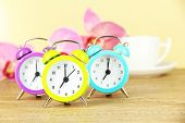 Colorful alarm clock on table on beige background