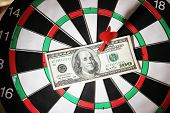 Money pierced by arrow on dartboard close up