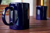 Pair Of Purple Mugs On A Wooden Table