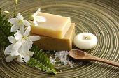 White frangipani and stacked soap with spoon on wooden plate