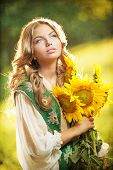 Young girl wearing Romanian traditional blouse holding sunflowers outdoor shot. Fairy tale