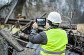 foto of collapse  - Building Inspector with tablet near collapsed building