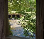 Creek Framed By Bridge Window
