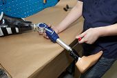 stock photo of prosthesis  - Worker in orthopaedic workshop adjusts leg prosthesis - JPG