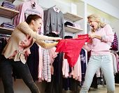 Image of two aggressive girls fighting for the last red tanktop in department store