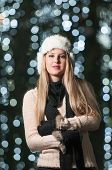 Fashionable lady wearing white fur cap and black muffler outdoor in Xmas scenery with blue lights