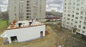 Workers build structure in residential district. View from unmanned quadrocopter