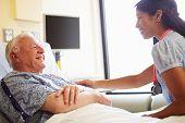 Female Doctor Talking To Senior Man In Hospital Room