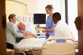 Medical Team Meeting With Senior Couple In Hospital Room