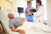 Medical Team Meeting As Senior Man Sleeps In Hospital Room