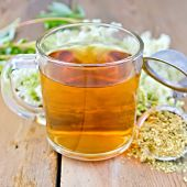 picture of meadowsweet  - Herbal tea in a glass mug metal sieve with dried flowers of meadowsweet fresh flowers of meadowsweet on a wooden boards background - JPG