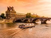 PARIS, FRANCE - AUGUST 25 2013:: Palais du Louvre by the Seine in beautiful orange Sun gleam, Paris