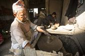 BHAKTAOUR, NEPAL - DEC 7, 2013 : Unidentified Nepalese man working in the his pottery workshop. More