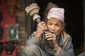 BHAKTAPUR, NEPAL - DEC 7, 2013: Portrait of unidentified Nepalese man smokes on the street. More 100