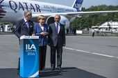 BERLIN, GERMANY - MAY 20, 2014: German Chancellor Angela Merkel (C) open up the International aviation and space exhibition ILA. The aircraft Airbus A350 XWB in background.
