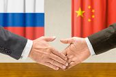 Representatives of Russia and China shake hands