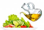 Healthy Vegetable Salad with Olive oil dressing isolated on white background. Pouring Olive oil. Hea