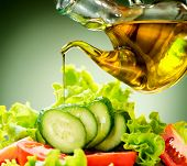 Healthy Vegetable Salad with Olive oil dressing. Pouring Olive oil. Healthy vegetarian food. Vegan. Diet, dieting concept. Lettuce, tomatoes, cucumbers. Organic bio food