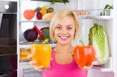 pretty girl hold red yellow pepper, refrigerator
