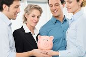 Group Of Businesspeople Together Holding Piggy Bank