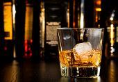picture of whiskey  - whiskey glass with ice in front of bottles on wood table - JPG