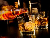 foto of whiskey  - barman pouring whiskey in front of whiskey glass and bottles on wood table - JPG