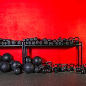 Kettlebells dumbbells and weighted slam balls weight training equipment at gym red wall