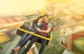 Happiness couple riding on ferris wheel at amusement park